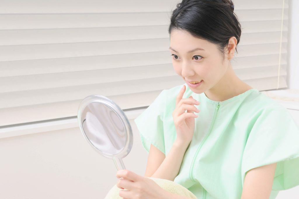 治療の後、鏡で顔を見て喜んでいる女性